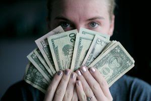 woman holding money after tax preparation season